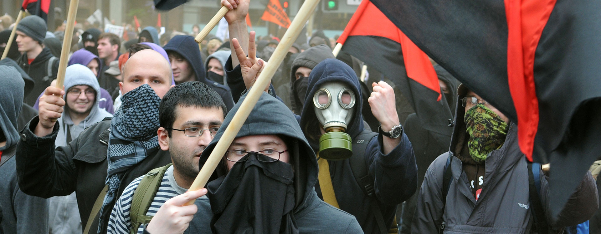 angry mob of protesters one wearing a gas mask