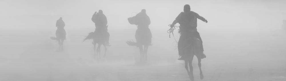 four horsemen riding in sandstorm