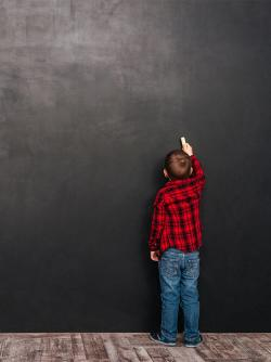 boy in flannel shirt drawing on a chalk board