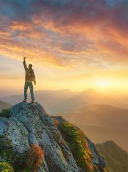 Man with arm upraised standing on mountain
