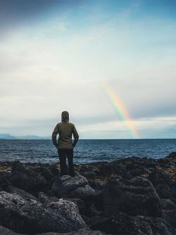 Woman watching rainbow over the sea