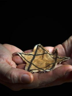 Hands cupping a tattered star of David