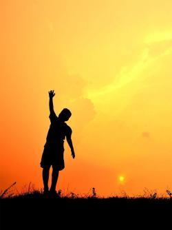 Boy with arm raised against orange sunset