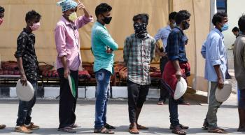 men wearing masks and waiting in line for food
