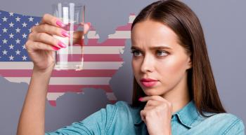 woman looking skeptically at a glass of water in front of a US map