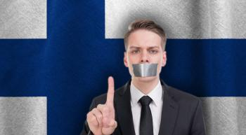 man with tape over his mouth in front of Finnish flag