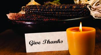 """Give Thanks"" sign in setting with corn cobs and glowing candle"