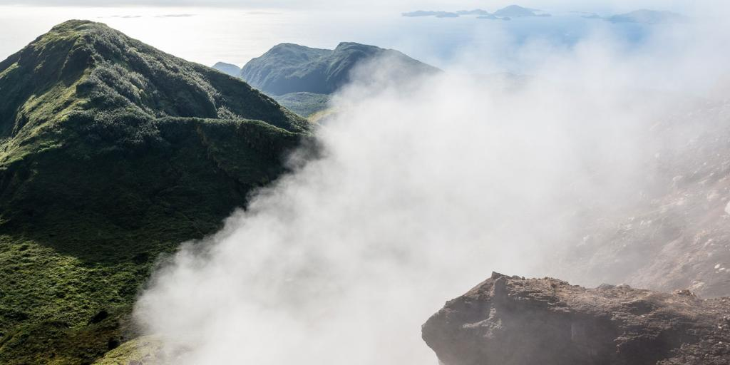 steam wafting from a tropical island mountaintop