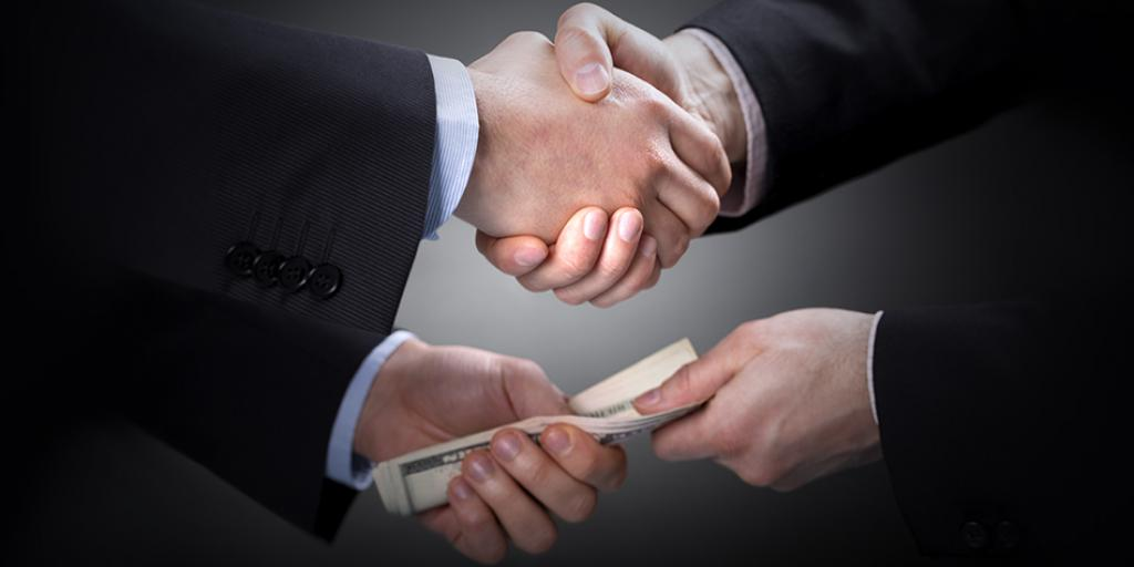 Politicians shaking hands and slipping each other a bribe.
