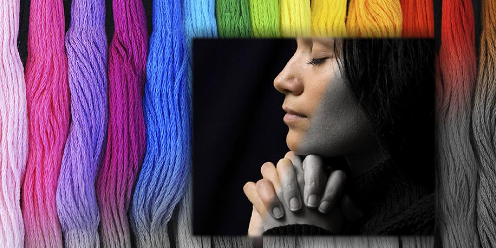 Woman praying, slowly turning from black and white into color, with stripes of vivid color in the background, fading from grey to rainbow shades.