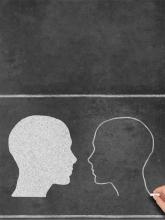 White and black heads or outlines drawn on a chalkboard