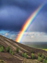 Rainbow on a hillside with storm clouds
